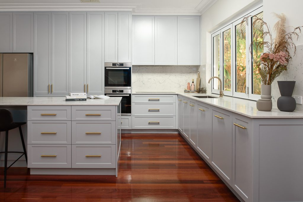 Newly renovated kitchen featuring White Attica Caesarstone benchtops and light grey cabinets.