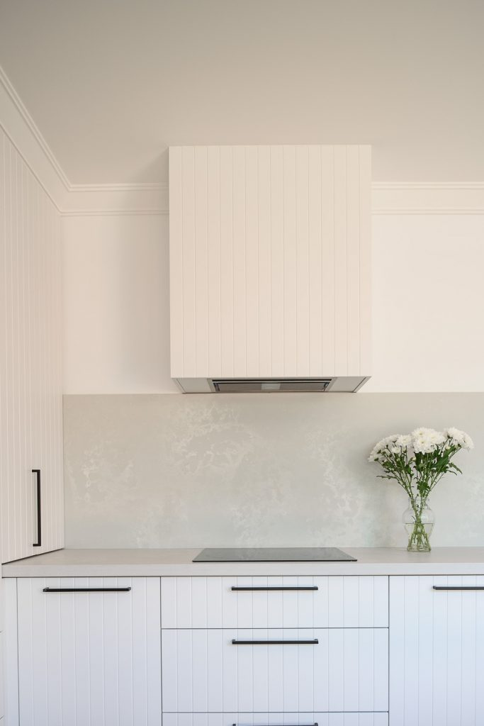 Renovated kitchen with rangehood and white cabinetry. Stone benchtop and splashback.