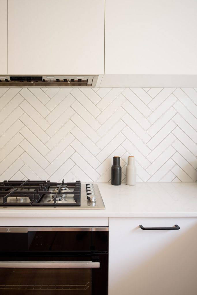 Renovated kitchen featuring white subway tile splashback laid in a herringbone pattern.