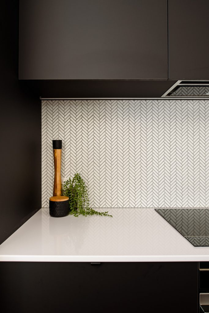 Renovated kitchen featuring white herringbone tile with black grout splashback
