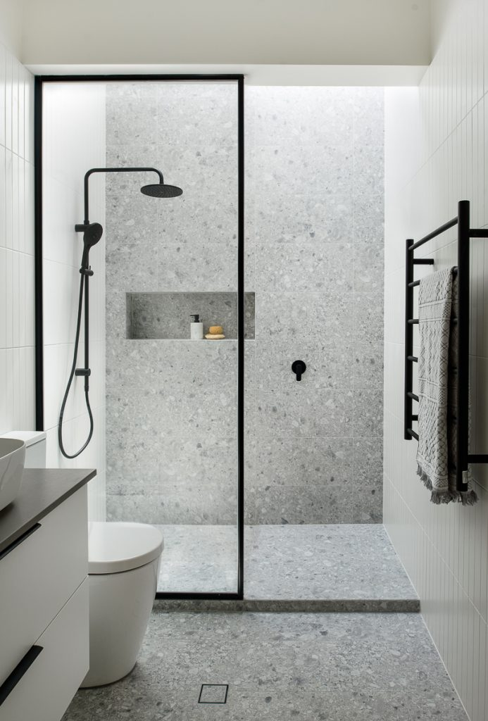 Renovated bathroom featuring grey tiles and black shower head with a skylight overhead.